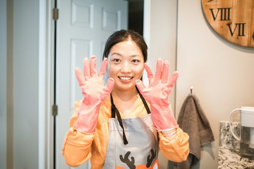 Woman Wearing Pink Latex Gloves and Gray Apron