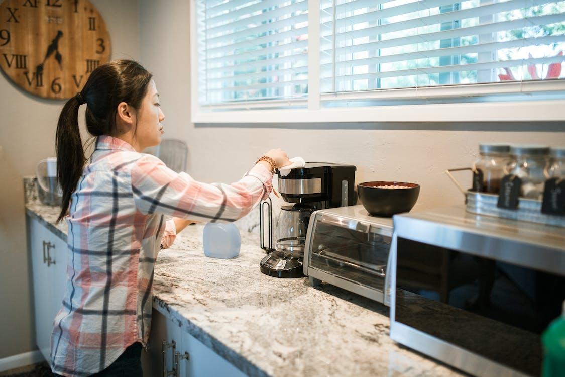 женщина в розово белой рубашке в клетку с серебряно черной кофеваркой