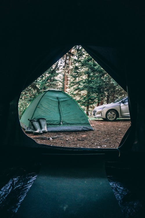 Camping tent in forest near car