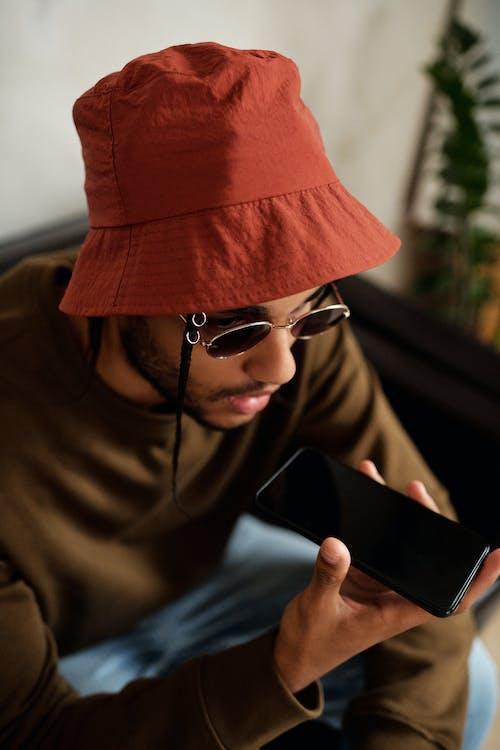 Pria Berkerudung Coklat Mengenakan Kacamata Berbingkai Hitam Memegang Smartphone Hitam