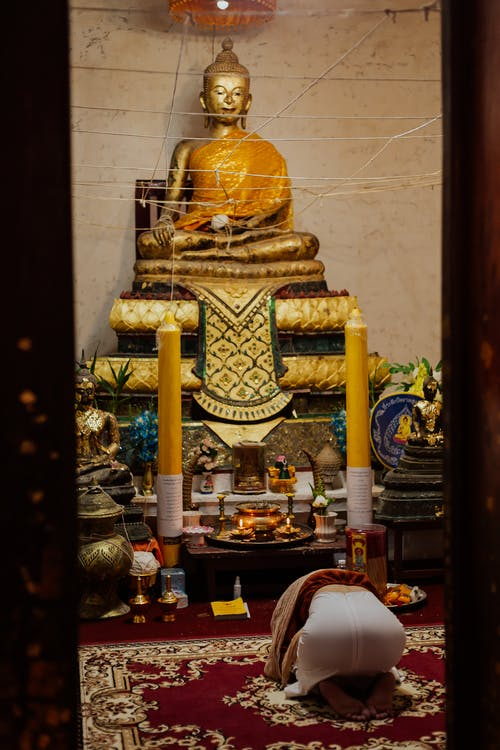 Gold Buddha Statue on Brown Wooden Table