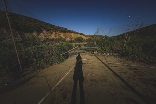 Shadow of anonymous person on empty abandoned sports ground with damaged mesh net fences located in mountainous terrain against cloudless blue sky