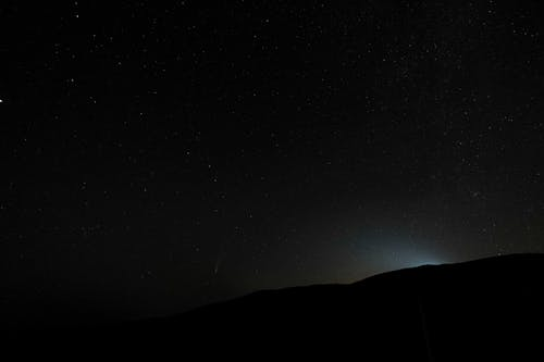 From below silhouette of mountain against dark night sky with shining stars in valley