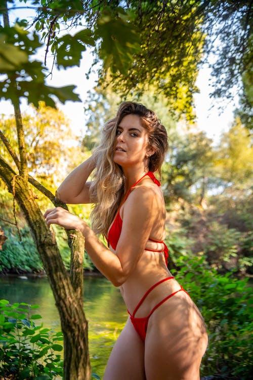 Woman in Red Bikini Standing Near Body of Water