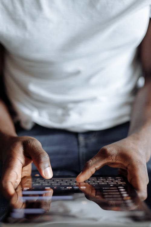 Person in White Shirt and Blue Denim Jeans Using Black Computer Keyboard