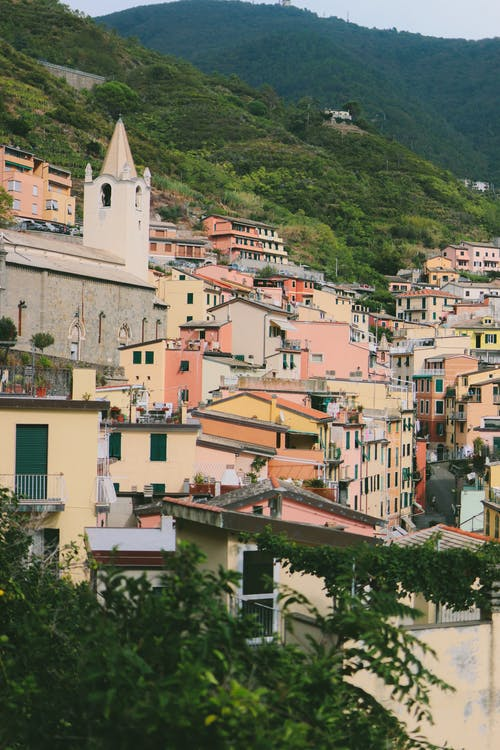 Picturesque view of old town with coloured houses and stone church surrounded with green hills and mountains