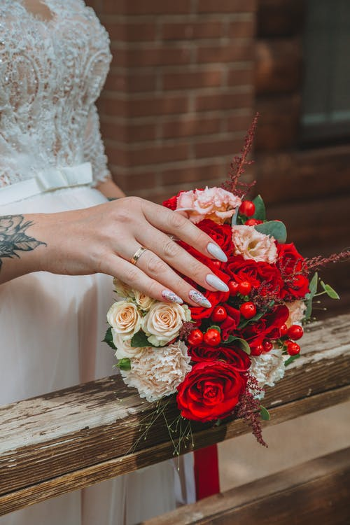 Unrecognizable female with manicured hand and wedding ring on finger touching gently bouquet of fresh flowers placed on wooden railing in daytime