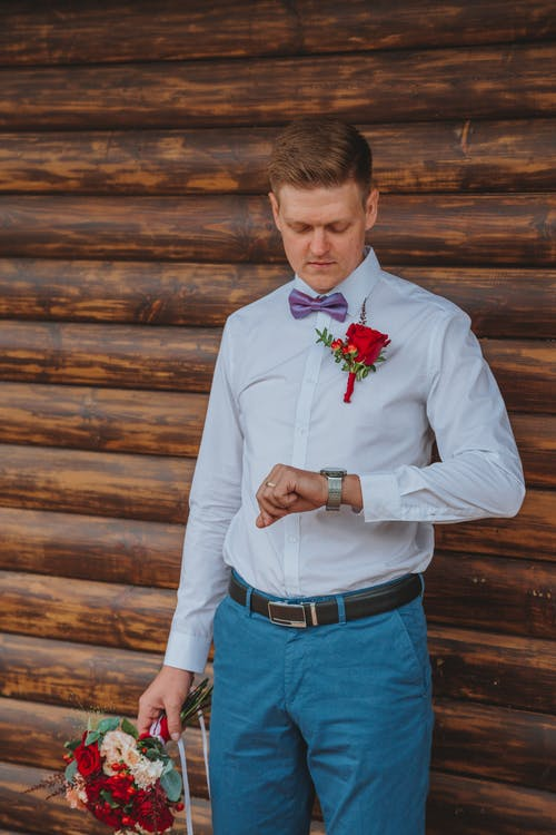 Elegant male wearing bow tie looking at wristwatch while standing near log wall with bouquet of flowers in hand in daylight