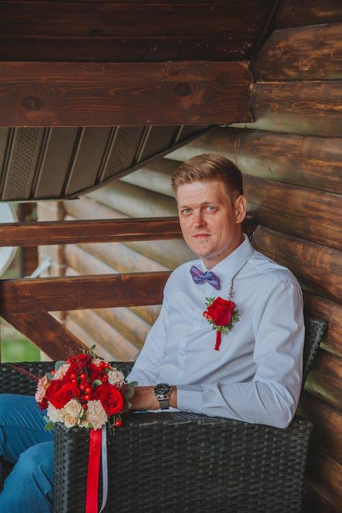 Cheerful groom sitting on street near log wall