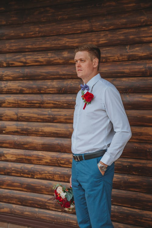 Pensive groom in elegant suit standing near log wall with hand in pocket and bouquet of flowers in hand while looking away