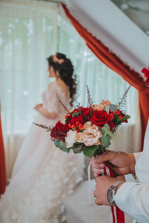 Crop groom with flowers near bride