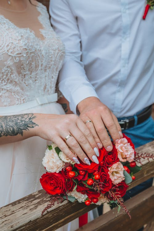 Unrecognizable bride and groom with wedding rings on fingers touching bouquet of beautiful flowers placed on wooden railing in daylight