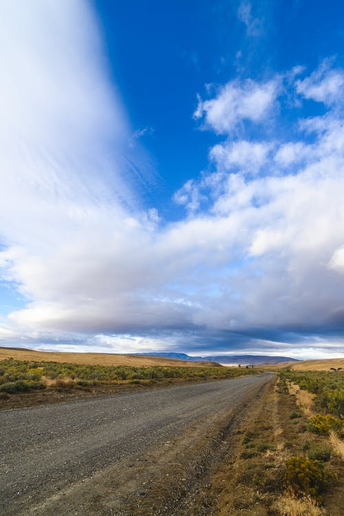 Empty straight asphalt road going through grassy terrain towards hills under cloudy sky