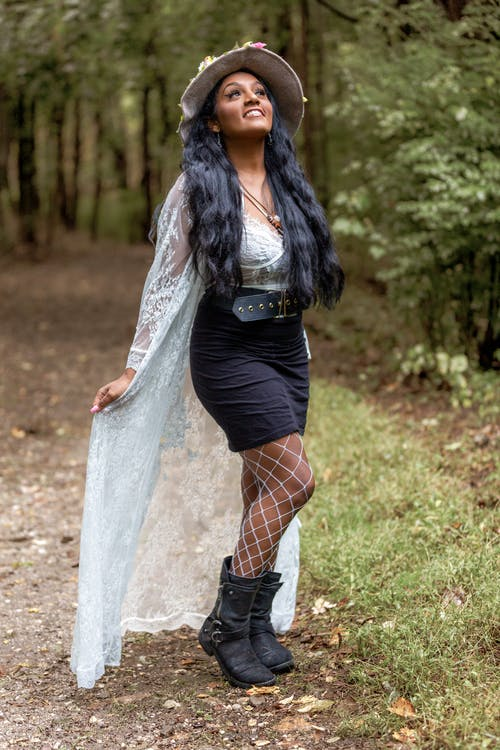 Dreamy black woman in strange clothes in forest
