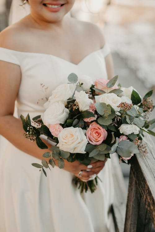 Crop bride with bouquet of flowers