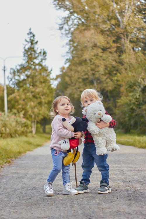 Girl in White Long Sleeve Shirt and Blue Denim Jeans Holding a Girl in White Long