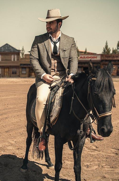 Man in Gray Coat Riding Black Horse