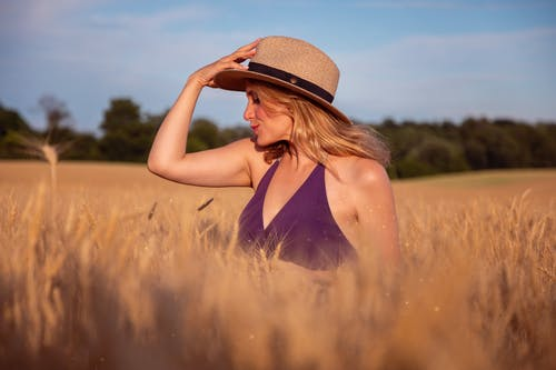 Woman in Black Spaghetti Strap Top Wearing Brown Straw Hat Standing on Brown Field