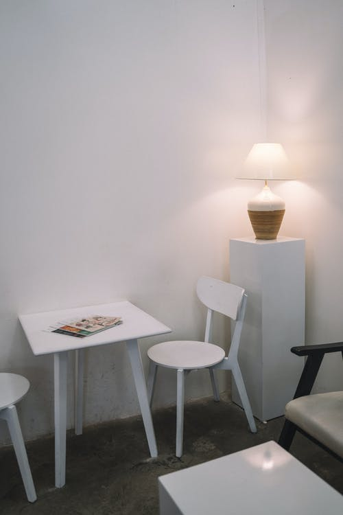 White Table and Chair on White Corner Wall
