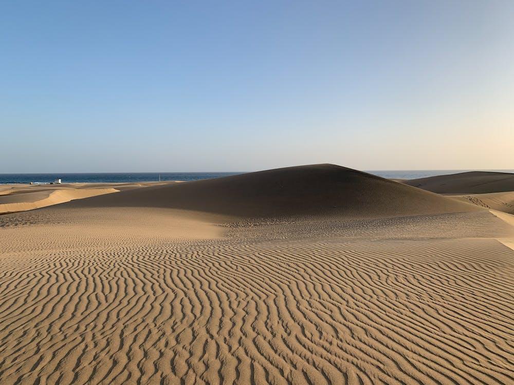 Brown Sand Field Under Blue Sky