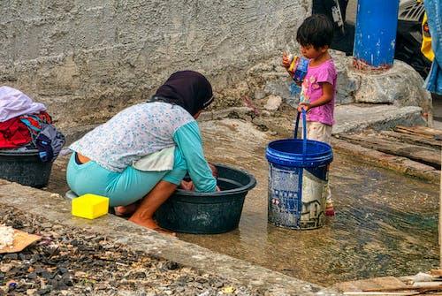 Unrecognizable ethnic woman washing baby on street