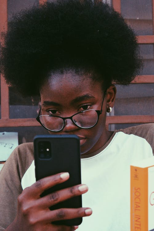 Crop focused black woman chatting on smartphone