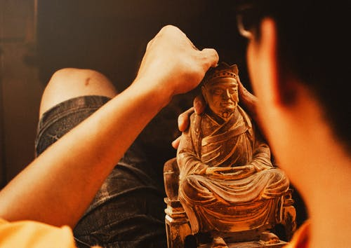 Person Holding Brown Figurine