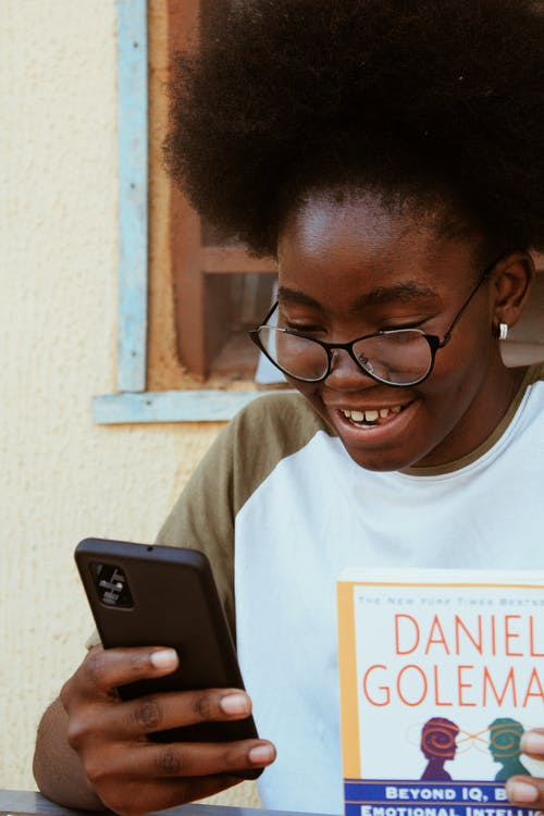 Crop smiling black woman with book surfing internet on smartphone