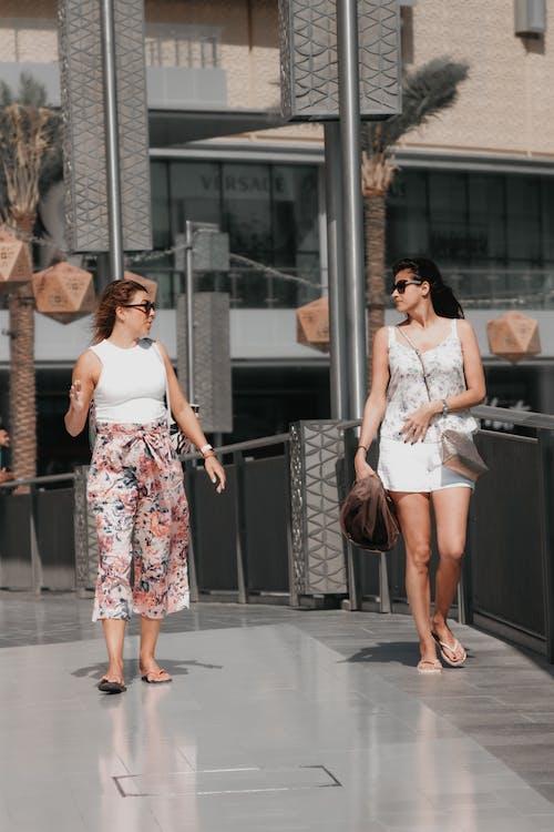 2 Women Standing Beside Glass Wall