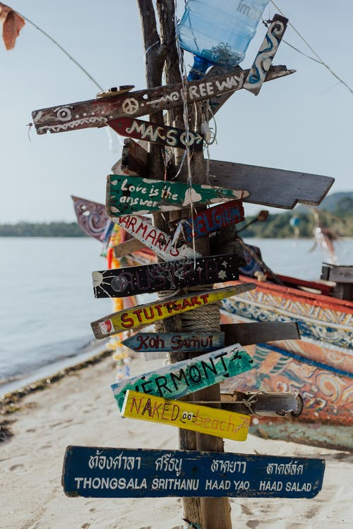 Black and White Wooden Signage on Beach