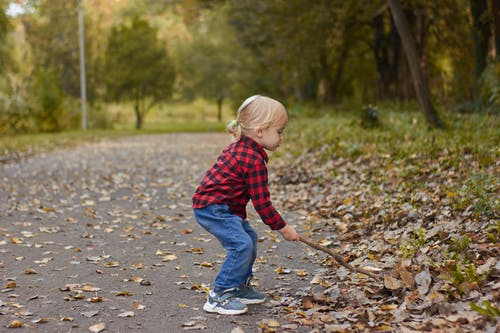 Child in Red and Black Plaid Dress Shirt and Blue Denim Jeans Walking on Gray Concrete