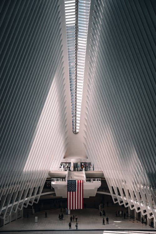 Interior of modern Oculus transportation hub at World Trade Center New York City Subway station with American flag hanging on center in sunny day