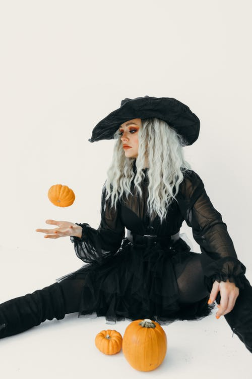 Woman in Black Witch Costume Catching A Pumpkin