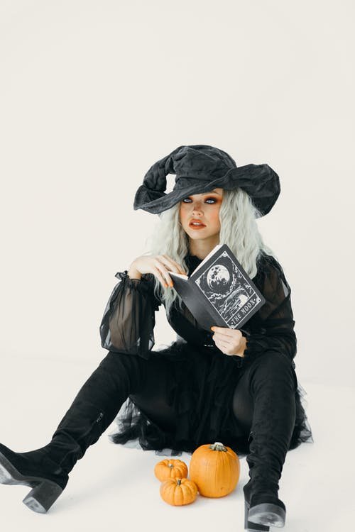 Woman in A Witch Costume Holding A Book