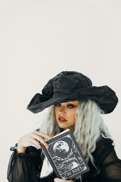 Woman in Black Witch Costume Holding Black and White Book