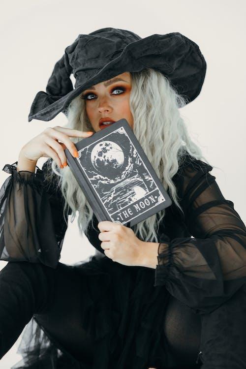 本を持つ魔女の衣装を着た女性