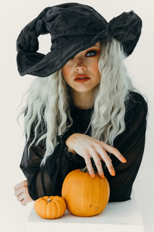 Woman in Black Witch Costume With Two Pumpkins