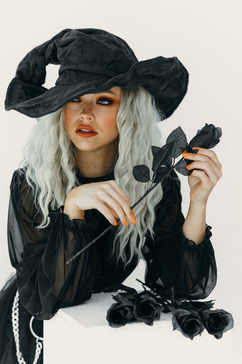 Woman in Black Witch Costume Holding Black Roses
