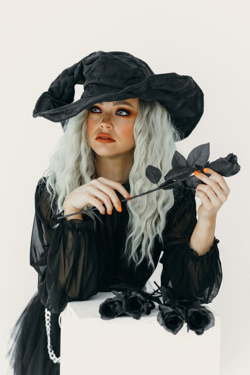 Portrait Of A Woman In Witch Costume Holding A Black Rose