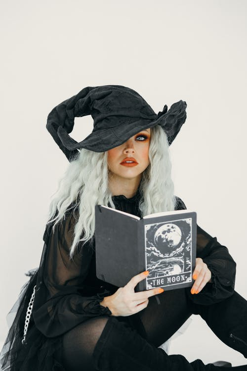 Woman in Witch Costume With A Black Book