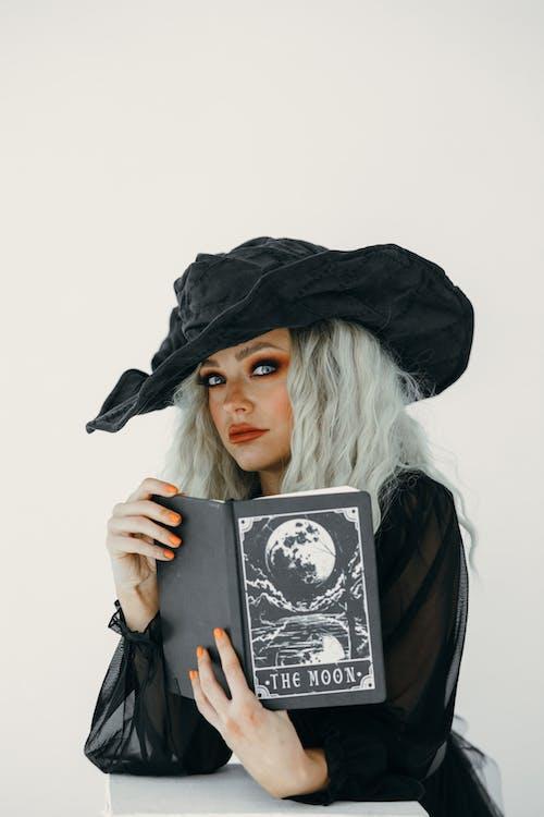 Retrato De Uma Mulher Vestida De Bruxa Segurando Um Livro Preto