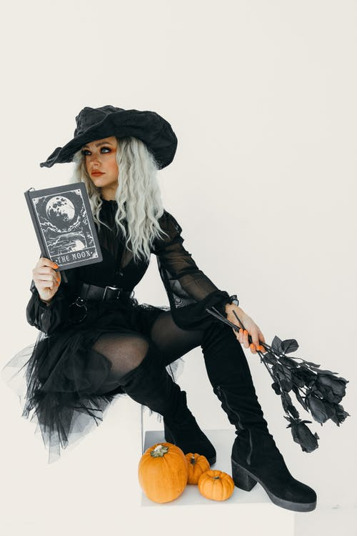 Woman in Black Witch Costume With A Book And Black Roses On Her Hands