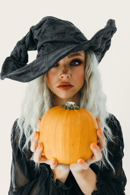 Woman in Black Witch Costume Holding Pumpkin