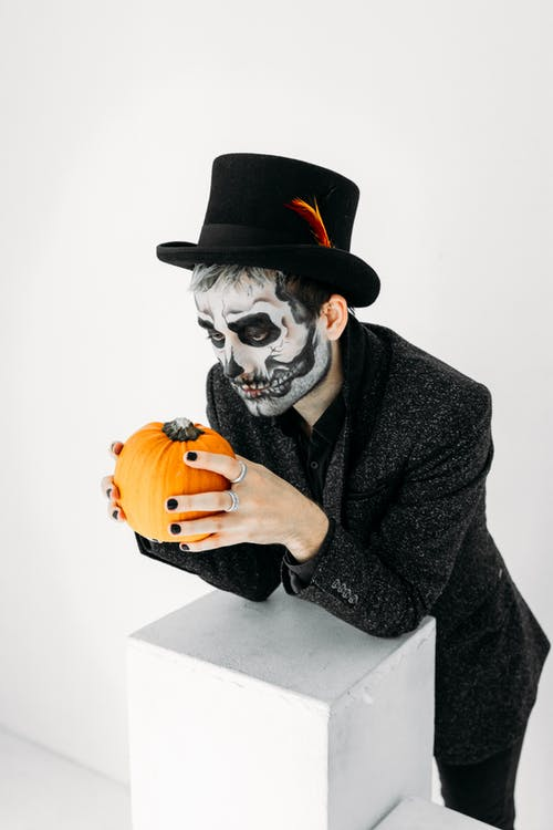 Man With A Scary Face Paint Holding A Pumpkin