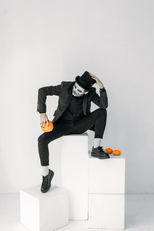 Man in Black Jacket and Black Pants Sitting on White Wall