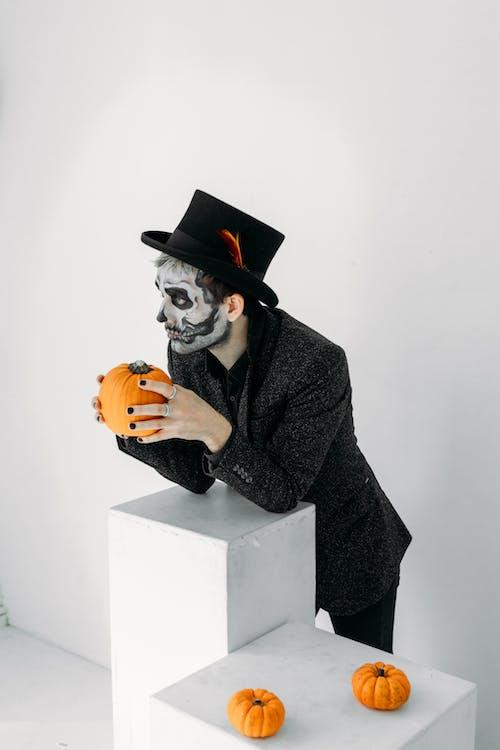 Man With Face Paint Holding A Pumpkin