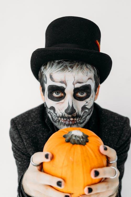 Man in Black and Skull Mask Holding Pumpkin