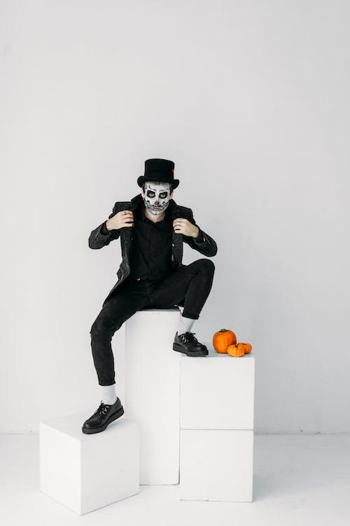 Beyaz Duvarda Oturan Siyah Elbiseli Adam