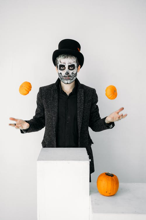 Man With Scary Face Paint Juggling Two Pumpkins
