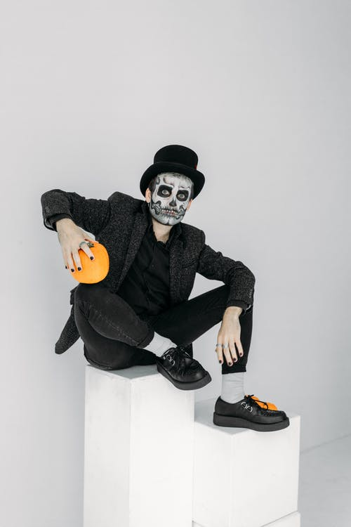 Man in Black Suit With Face Paint
